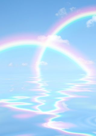 Fantasy abstract of double rainbows against a blue sky with reflection over rippled water. Stock Photo