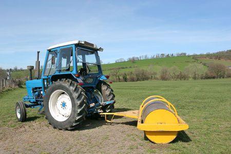 holgaz�n: Tractor con rodillo de color amarillo permanente adjunto de inactividad en las tierras agr�colas en las zonas rurales de campo en primavera. Los agricultores rollo de pasto en la primavera para promover el crecimiento. Foto de archivo