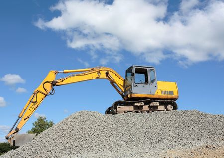 holgaz�n: Excavadora industrial ociosa de pie encima de un mont�n de grava frente a un cielo azul con nubes.