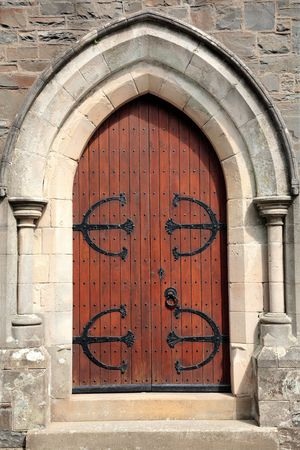 Old wooden oak arched gothic church doorway with black wrought iron hinges, studs and door knocker. Set into a stone framework.