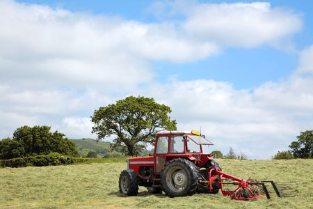 clouds making: Red tractor with swather to the rear, (hay making equipment) standing idle in a field in summer with freshly cut hay. Blue sky and clouds to the rear.