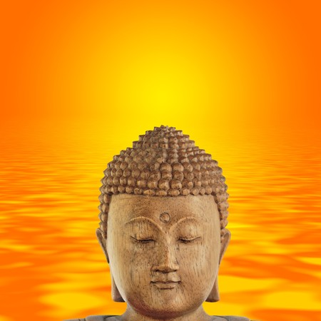 Buddha head with eyes closed in prayer and smiling, with a golden sunset over rippled water to the rear. photo