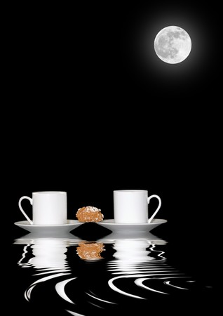 Abstract of two white china coffee cups and saucers with sugar coated biscuit and reflection over rippled water against black background with full moon. Stock Photo