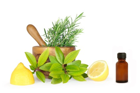 aromatherapy oils: Rosemary and bay herb leaf selection with half a lemon, olive wood pestle and mortar and brown glass aromatherapy bottle. Over white background. Stock Photo
