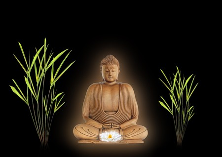 smiling buddha: Buddha with golden aura in prayer holding a glowing white lotus lily flower with bamboo grass either side. Over black background Stock Photo