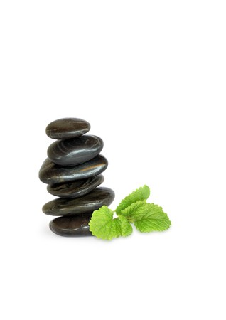 Spa massage stones in perfect balance with a leaf sprig of lemon balm herb to one side, over white background. photo