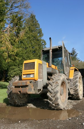 Four wheel drive tractor standing idle on a driveway with a large puddle. Set against a clear blue sky with trees to one side. photo