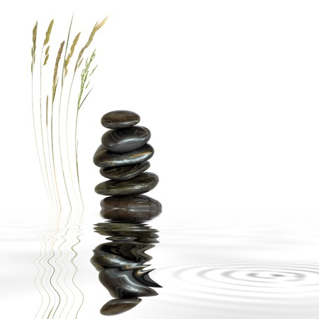 Zen abstract of black spa massage stones in perfect balance with natural grass and reflection in rippled grey water, over white background. Stock Photo - 4209648