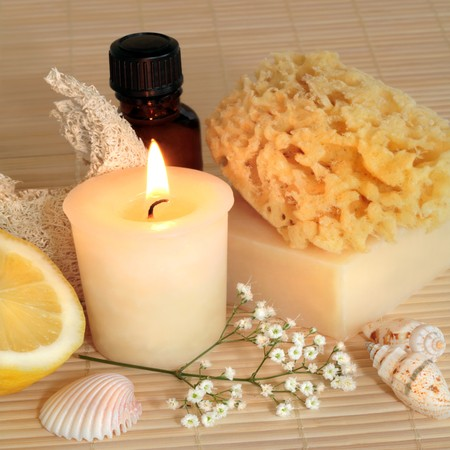 Natural cleansing products lit by a candle, consisting of a sponge, soap, brown essentail oil glass bottle, exfoliating sponge, fresh lemon half, and shells with a spray of gypsophila white flowers. Set against a bamboo background. photo
