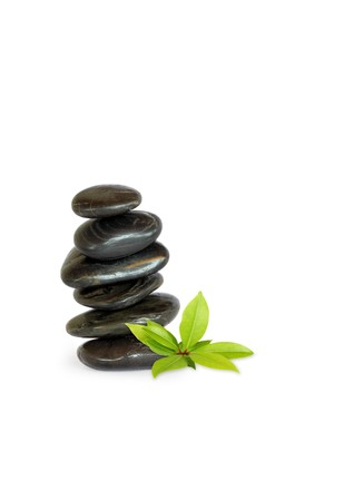 Spa massage stones stacked in perfect balance with bay leaf sprig, over white background. photo