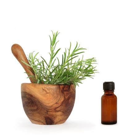 vijzel: Rozemarijn kruid laat in een olijf houten vijzel met stamper en aromatherapie bruine glazen fles op witte achtergrond.