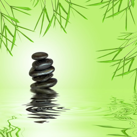 enduring: Zen garden abstract of black spa massage stones in perfect balance with bamboo leaf grass