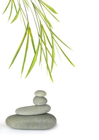 Zen abstract design of grey spa stones in perfect balance with bamboo leaf grass, over white background. Stock Photo - 4408104