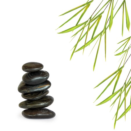 Zen abstract design of black spa treatment stones in perfect balance with bamboo leaf grass, over white background. Stock Photo