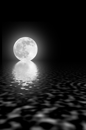equinox: Abstract of a full moon on the spring equinox with reflection over rippled water against a black sky.