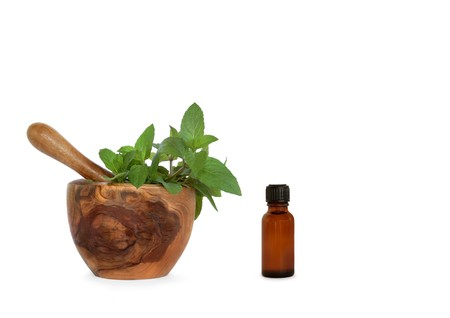 Chocolate mint herb leaves in an olive wood mortar with pestle and aromatherapy essential oil bottle, over white background. photo