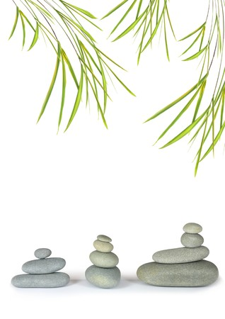 Zen abstract design of grey spa stones in perfect balance with bamboo leaf grass, over white background. Stock Photo - 4485925