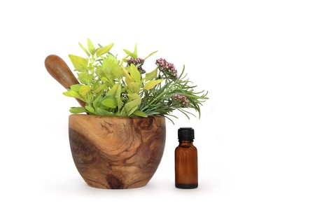 Rosemary, oregano and marjoram herb leaves and flowers in an olive wood mortar with pestle and  aromatherapy essential oil bottle, over white background. Stock Photo - 4534955