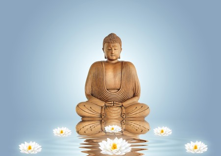 Buddha in meditation and lotus lily flowers with reflection over rippled water, set against a blue background with white central glow. Stock Photo