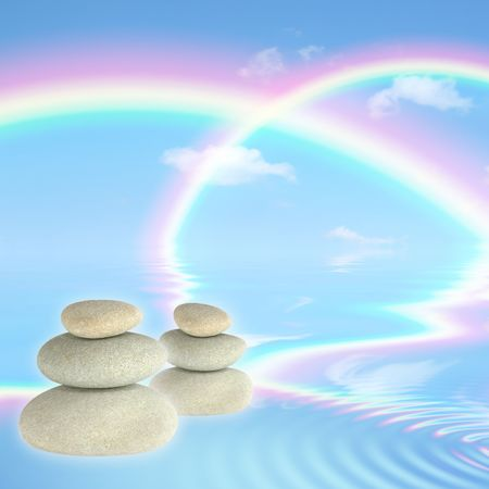 Fantasy abstract of double rainbows against a blue sky with reflection over rippled water and floating grey spa stones in perfect balance. Stock Photo