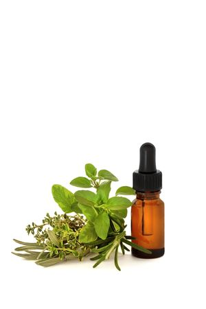 Herb leaf selection with an aromatherapy essential oil dropper bottle, over white background. photo