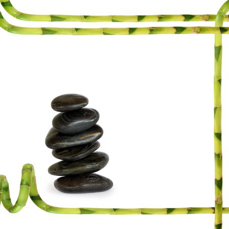 holistic:  Spa  massage treatment stones in perfect balance with a lucky bamboo leaf grass abstract frame, over white background.