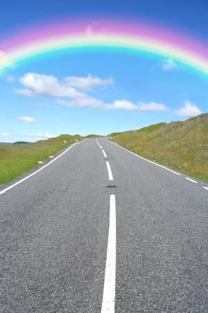 en mont�e: Uphill de routes rurales avec un arc en ciel et le ciel bleu et nuages dans le lointain.