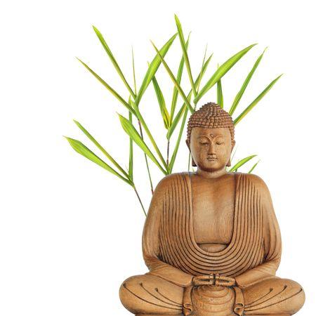Buda en meditación con hierba de hojas de bambú, sobre fondo blanco.  Foto de archivo