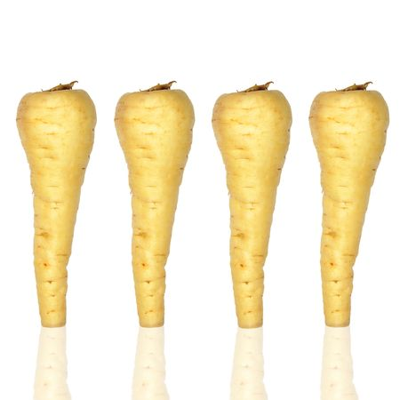 parsnips: Four raw parsnips in a line over white background.