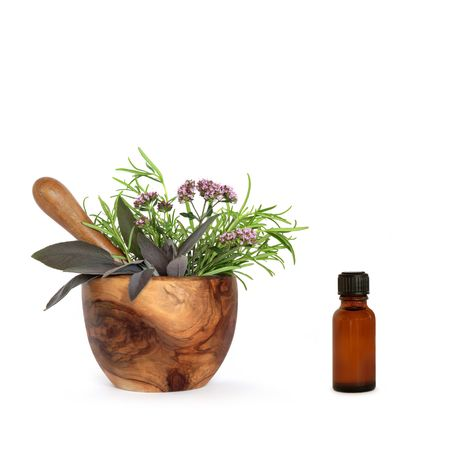 Rosemary, sage and marjoram herb leaves and flowers in an olive wood mortar with pestle and aromatherapy  essential oil bottle, over white background. Stock Photo - 4909650