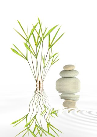 healing with chi: Zen abstract of grey spa pebbles in perfect balance and bamboo leaf grass with reflection in rippled water, over white background.