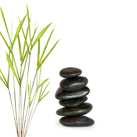 Zen abstract of grey spa treatment stones in perfect balance with bamboo leaf grass, over white background.