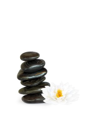 Spa massage treatment stones in perfect balance with a japanese lotus lily, over white background.  photo