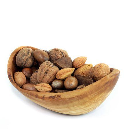 alergenos: Nuez de la selecci�n en un cuenco de madera de olivo de Brasil, nueces, almendras, avellanas y pacanas, sobre fondo blanco.