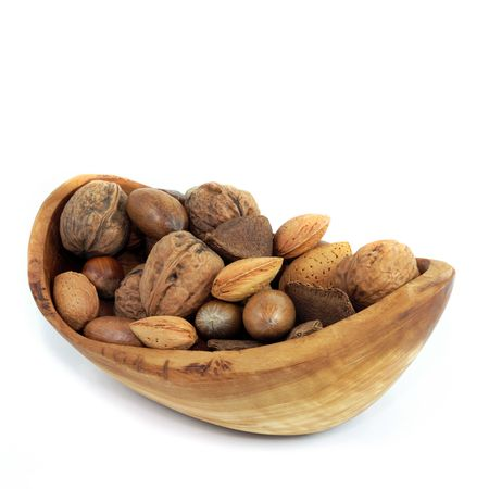 allergens: Nut selection in an olive wood bowl of brazils, walnuts, almonds, pecans and hazelnuts, over white background. Stock Photo