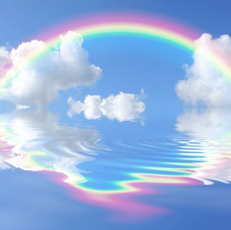Rainbow fantasy abstract with reflection over rippled water set against a blue sky with clouds background.