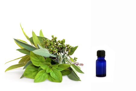 Herb leaf and flower selection  with a blue glass essential oil bottle, over white background. Stock Photo - 5111506