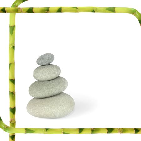 Zen abstract of grey spa massage treatment stones in perfect balance with lucky bamboo grass stems forming a frame, over white background. photo