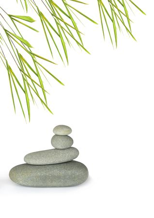 Grey spa treatment stones in perfect balance with bamboo leaf grass, over white background. photo