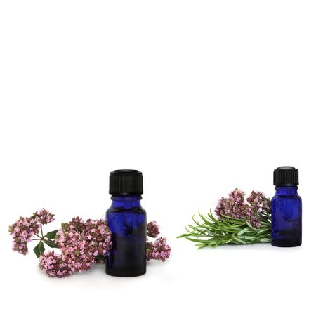 Rosemary herb leaf sprigs and marjoram flowers with aromatherapy essential oil glass bottles, over white background.
