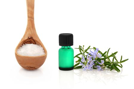 stimulating:  Rosemary herb leaf sprig in flower with a green aromatherapy essential oil bottle and sea salt in an olive wood ladle, over white background.