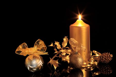Golden christmas decorations in candlelight including sparkling baubles, ribbon, holly and pine cone, over black background with reflection. photo