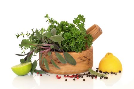peppercorns:  Parsley,  sage, rosemary and thyme herb leaves in an olive wood mortar with pestle, with lemon and lime halves and peppercorns, over white background with reflection. Stock Photo