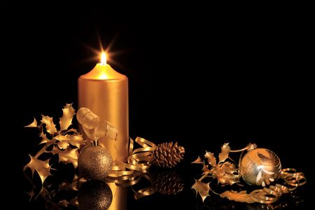 christian candle: Golden christmas decorations in candlelight with  baubles, ribbon, holly, oak leaves and pine cone, over black background with reflection.