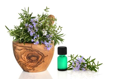 Rosemary and thyme herbs in flower in an olive wood mortar with pestle with an aromatherapy oil glass bottle and leaf sprig isolated over white background. Stock Photo - 5566333