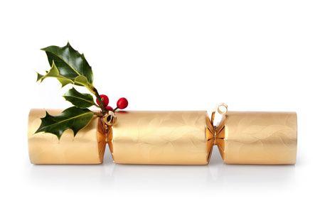 galletas integrales: Golden christmas cracker con una ramita de hojas de acebo con bayas de color rojo, sobre fondo blanco con la reflexi�n.