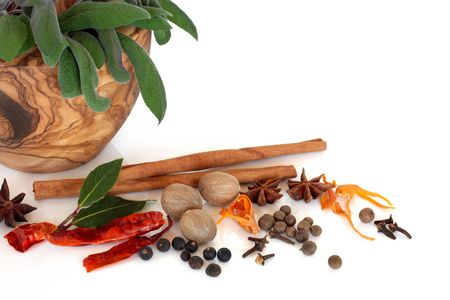 Spice selection and bay herb leaves with fresh sage in an olive wood mortar with pestle, over white background. photo