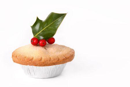 carne picada: Pastel de picadillo de Navidad cubierto con hojas de acebo y bayas rojas, sobre fondo blanco.  Foto de archivo