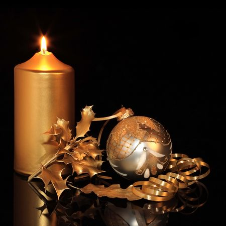 candlelit: Christmas silver bauble with golden oak and holly leaves and ribbon, lit by a  candle, set against black background with reflection.