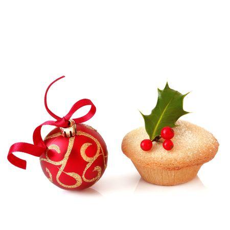 carne picada: Pastel de carne picada de Navidad con una ramita de hojas y bayas de acebo y oropel espumosos rojo y oro, sobre fondo blanco.
